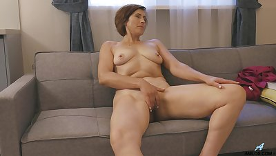 Horny mature model Eleanor fingers her pussy and plays with her tits